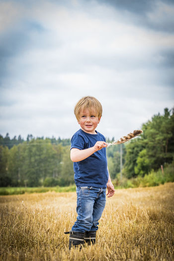Agriculture Boys Casual Clothing Childhood Cloud Cloud - Sky Crop  Day Elementary Age Enjoyment Field Focus On Foreground Front View Grass Growth Holding Innocence Leisure Activity Lifestyles Nature Person Plant Rural Scene Sky Standing