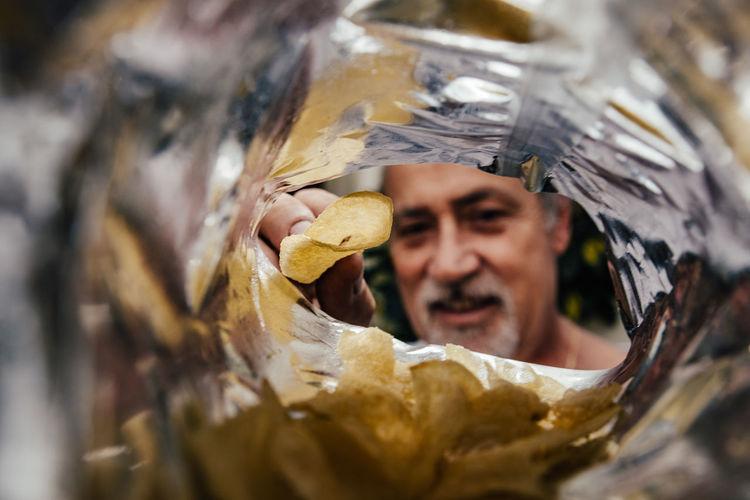Close-up portrait of man holding leaf