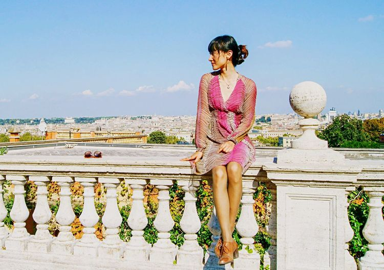 Beautiful Woman Sitting On Balustrade Against Sky