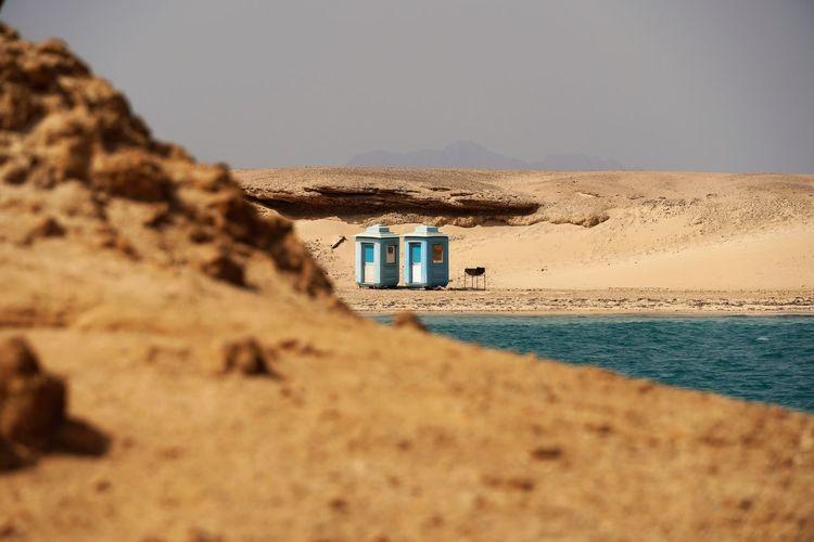 Lifeguard hut on sand at beach against clear sky