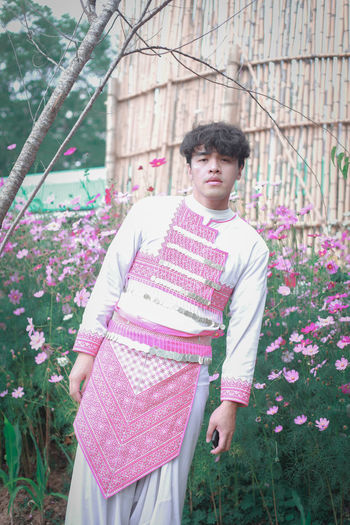 Full length of young man standing against pink flowering plants