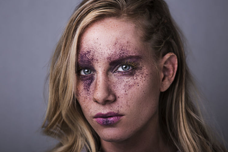 Close-up portrait of woman with purple bruise make-up against gray background