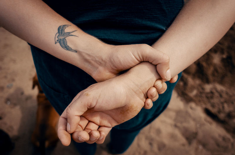 A tattoo of a swallow bird sits on the folded arms of a young female on a beach in Whitby, England, UK, on August 20, 2018. Human Hand Hand Human Body Part Real People Tattoo Focus On Foreground People Close-up Lifestyles Body Part Men Midsection Adult High Angle View Land Finger Human Finger Women Human Limb Ink Inkedgirls Inked Shallow Depth Of Field Fingernail Sand Pose Denim Golden Hour