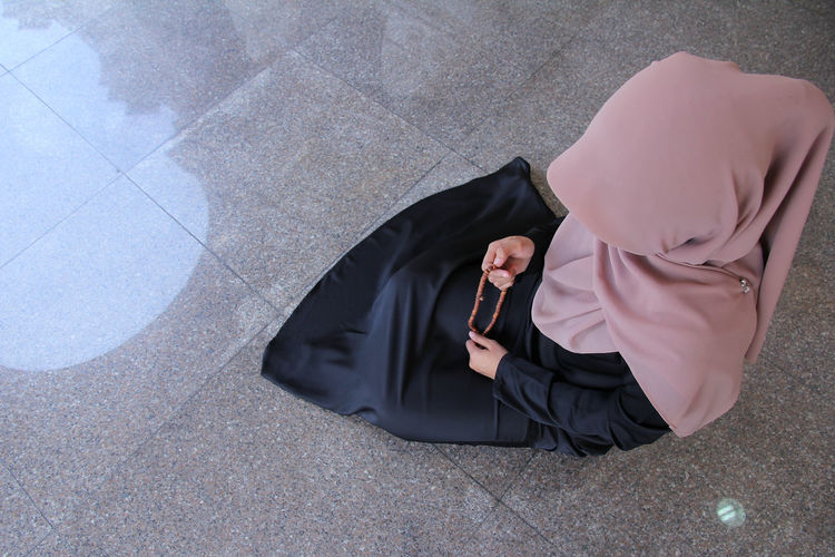High angle view of woman in hijab holding counting rosary beads while praying at mosque