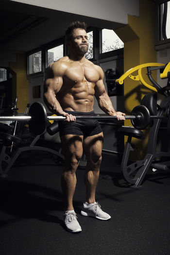 Close-up of muscular man holding dumbbell at gym