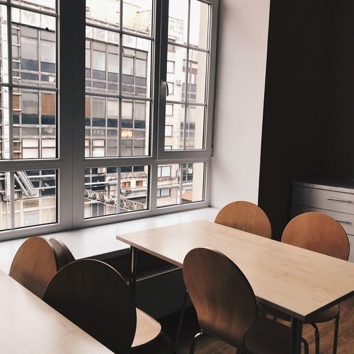 Empty chairs and table arranged by window in cafe