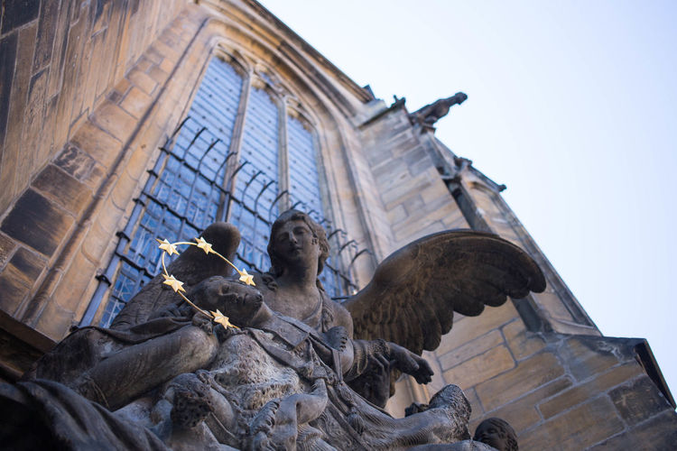 Low Angle View Of Angel Sculpture By St Vitus Cathedral Against Clear Sky