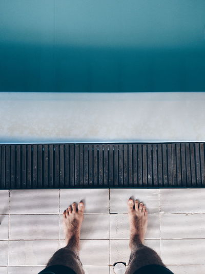 Low section of man standing by swimming pool