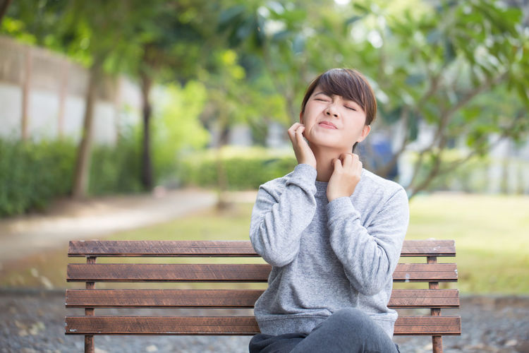 Young woman scratching neck while sitting on bench at park