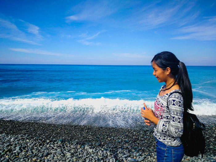 Young woman standing on beach against sky