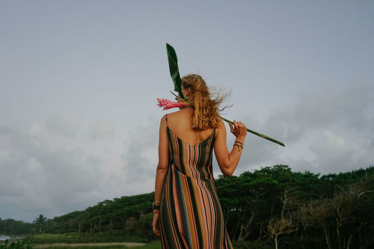 Woman standing by plants against sky