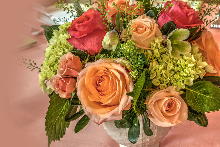 Pale peach roses, green hydrangea, and pink roses in a bouquet on a table display for dinner. Rosé Freshness Rose - Flower Plant Flower Flowering Plant Beauty In Nature Close-up Nature Flower Head Flower Arrangement Bouquet Peach Pink Color Green Hydrangea Hydrangea Spring Bouquet Flowers Decorations Femininity Romantic Sky Romantic