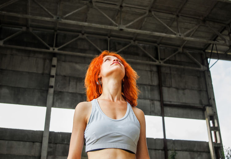 Redhead woman looking up while wearing sports bra