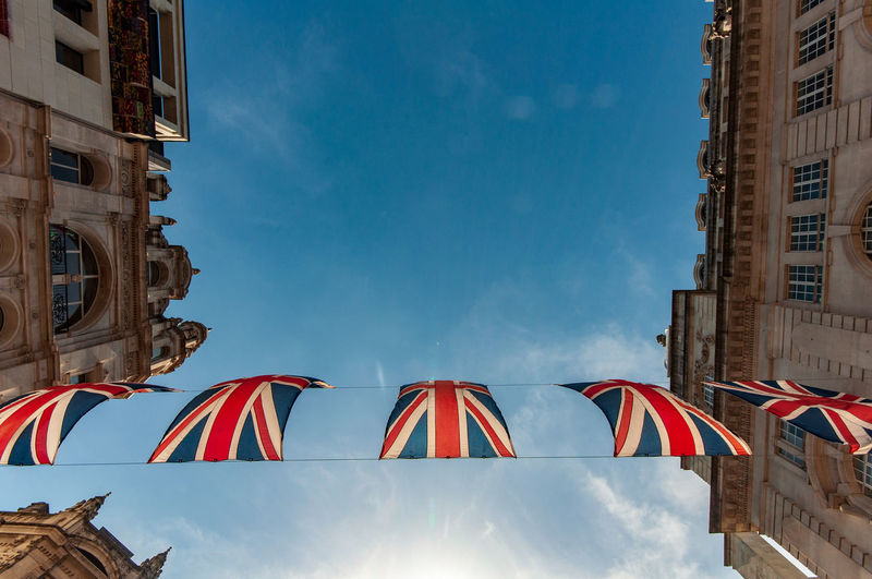 Low Angle View Of British Flags Against Buildings Against Sky