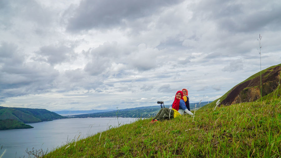 Female friends sitting on grassy hill by lake toba against sky