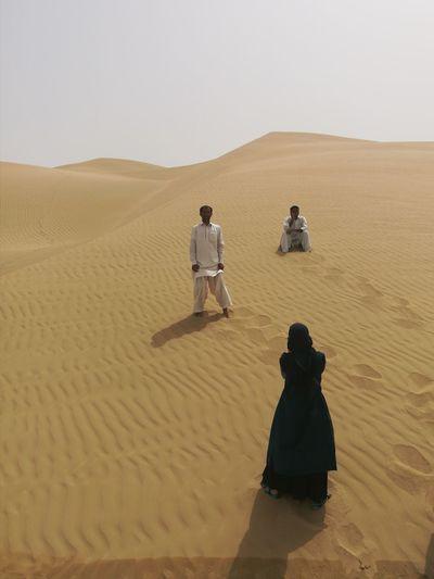 Friends On Sand Against Sky