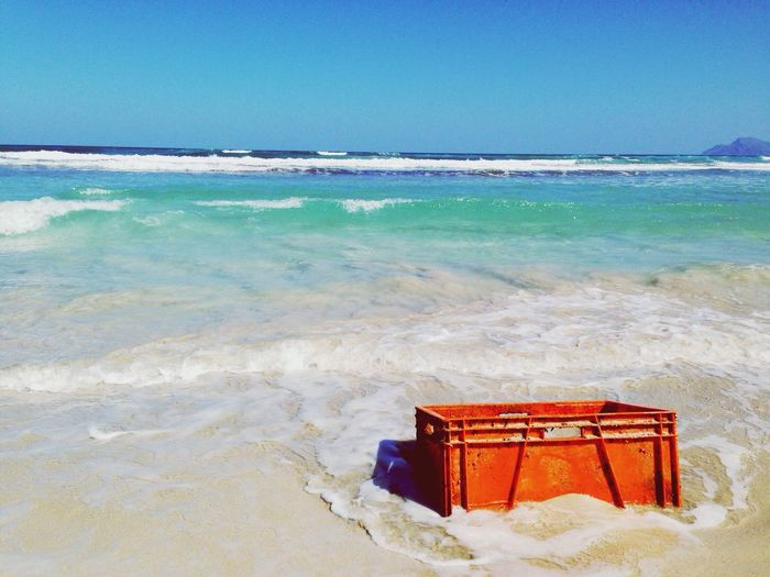 Abandoned Crate At Sea Shore Against Clear Sky