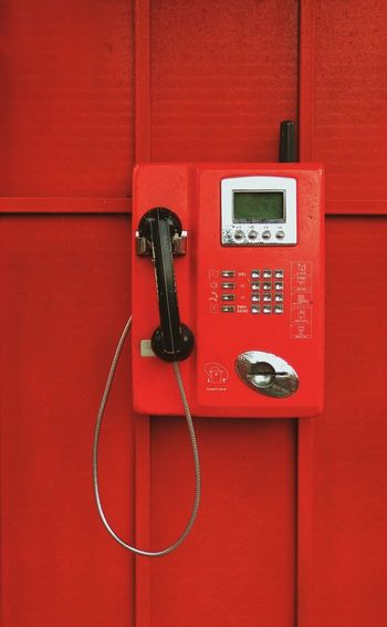 Close-up of telephone booth against red wall