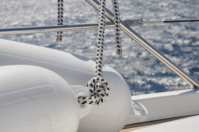 Close-up of rope tied on metal against sea
