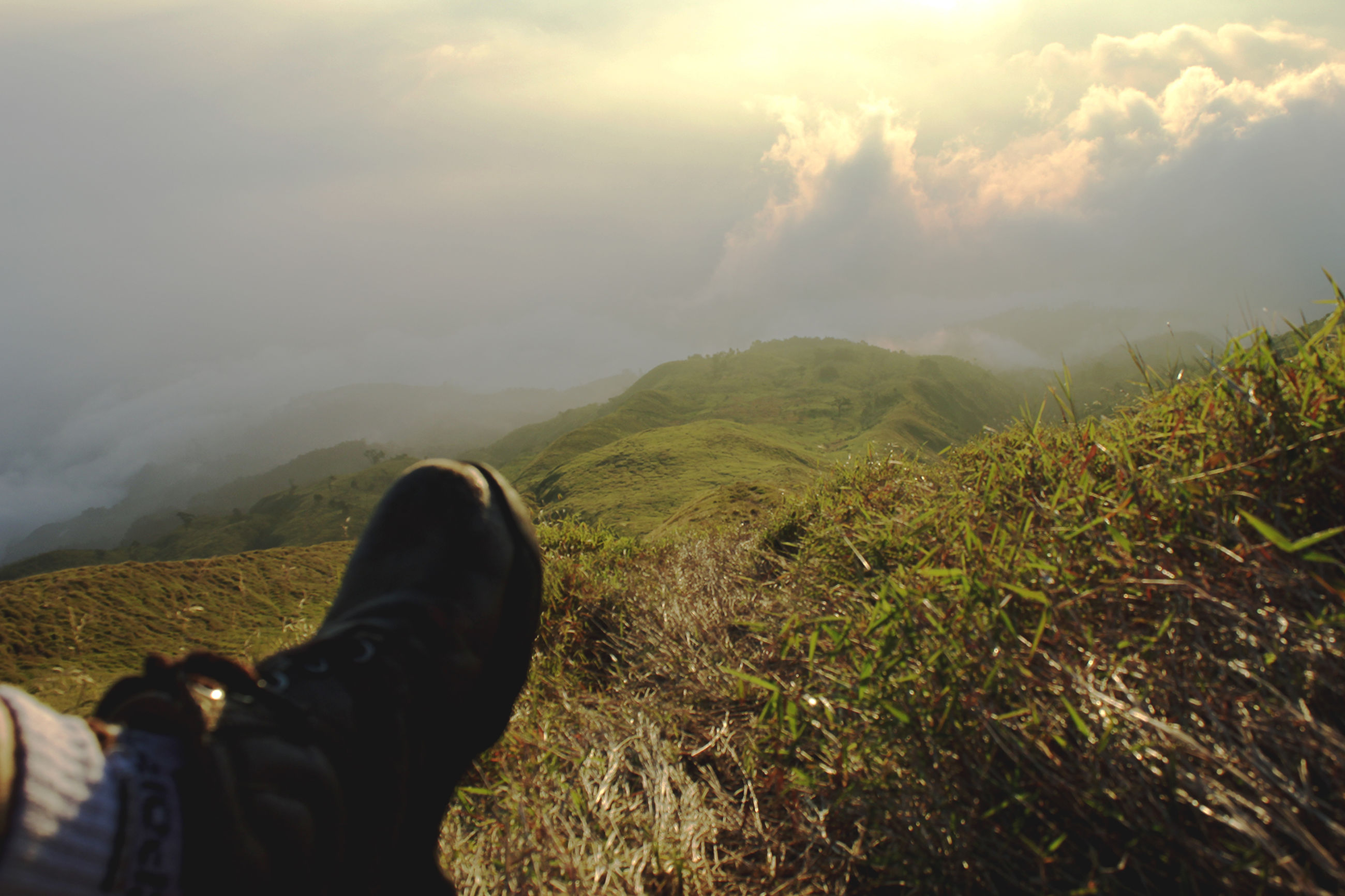 mountain, nature, one person, personal perspective, human leg, landscape, human body part, beauty in nature, cloud - sky, outdoors, real people, sky, day, low section, scenics, adventure, men, grass, human hand, people