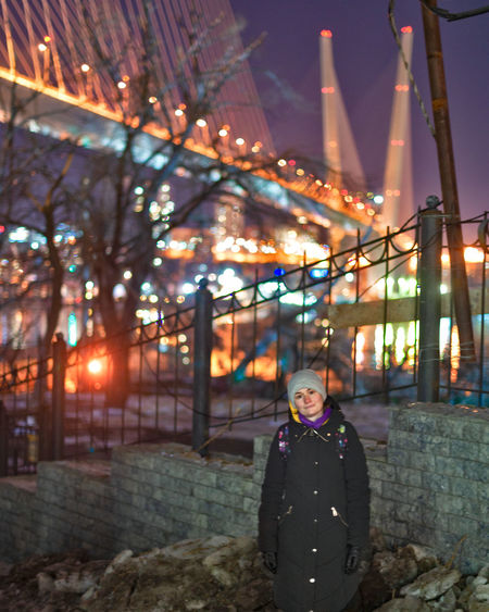 Portrait of woman standing against illuminated lights at night