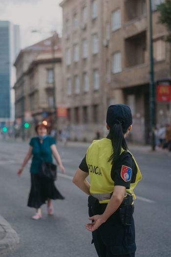Rear view of women walking on city street
