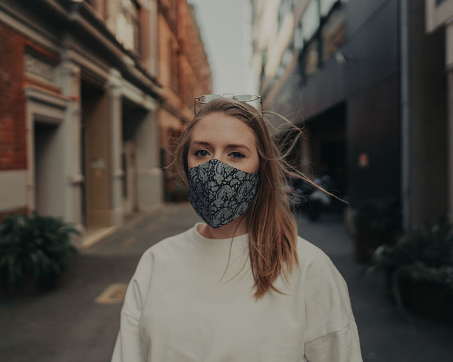 Portrait of beautiful woman wearing mask standing on street in city