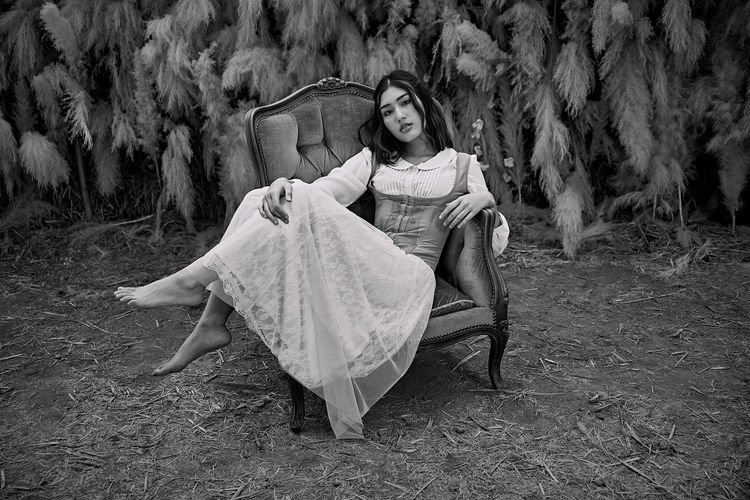 Portrait of a beautiful young woman lying on land