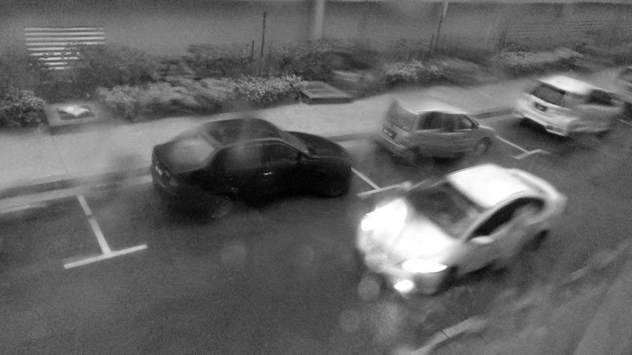 High angle view of car on road seen through wet window