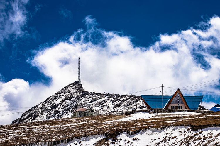 Building on snow covered mountain against sky