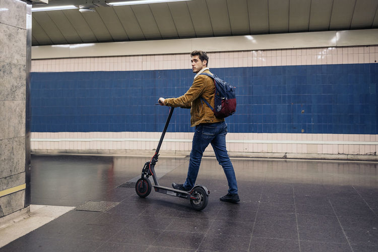 Full length of man with electric push scooter standing on subway station