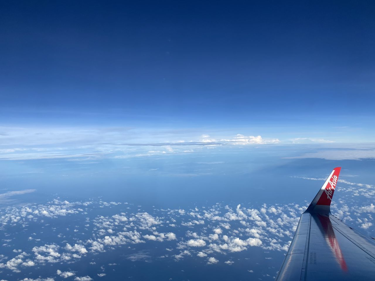 AERIAL VIEW OF AIRPLANE FLYING OVER BLUE SKY