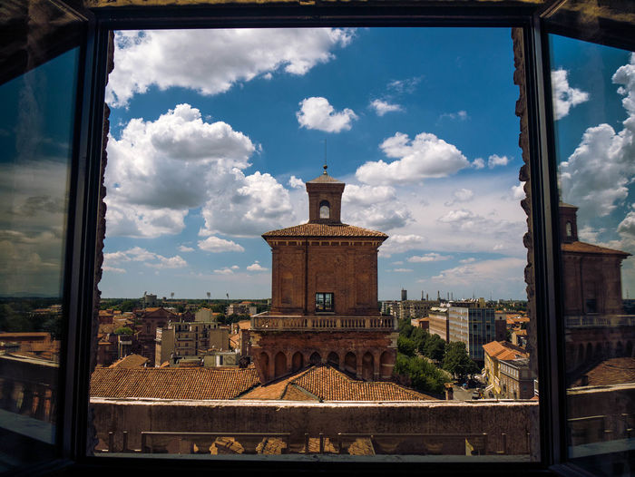 Buildings against sky seen through glass window
