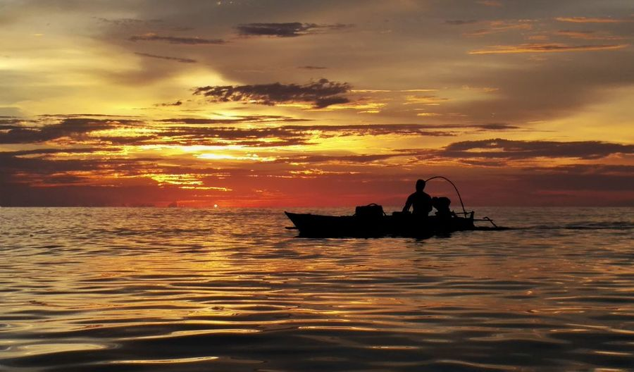 Silhouette man sitting in boat on sea during sunset