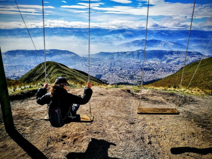 Rear view of woman sitting swing at mountain against sky