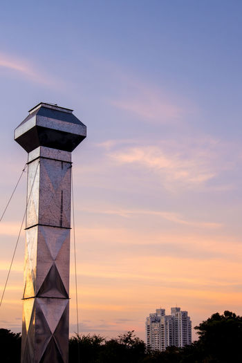 Tower on silhouette of building against sky at sunset