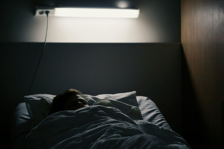 Man sleeping on bed in illuminated bedroom