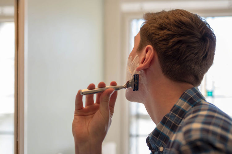 Close-Up Of Young Man Shaving At Home