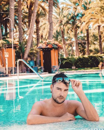 Portrait Of Handsome Man With Sunglasses In Swimming Pool