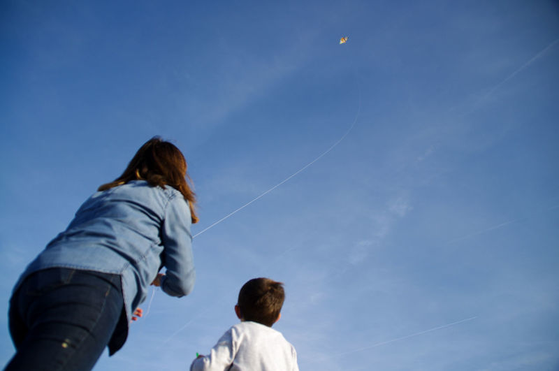 Low angle view of mother flying kite by son against sky