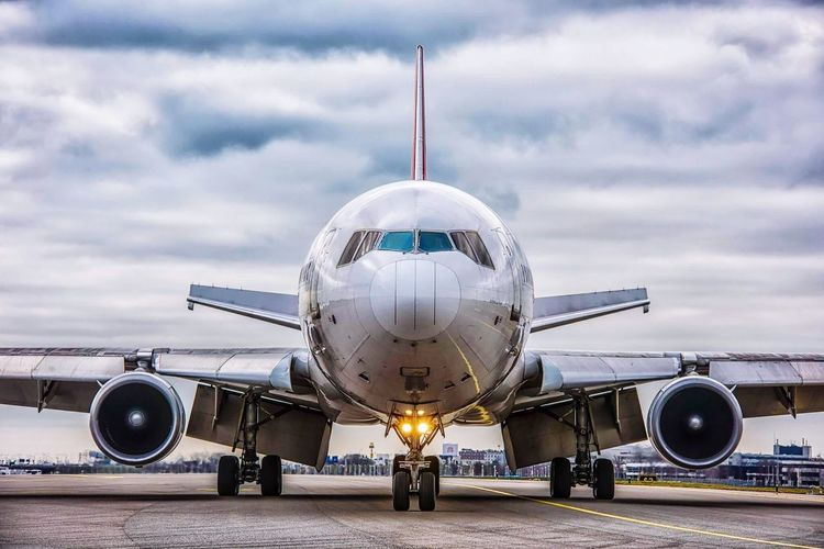 Airplane on airport runway against cloudy sky