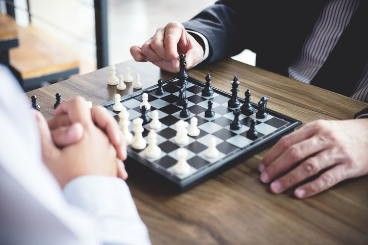 Midsection of business people playing chess on wooden table in office