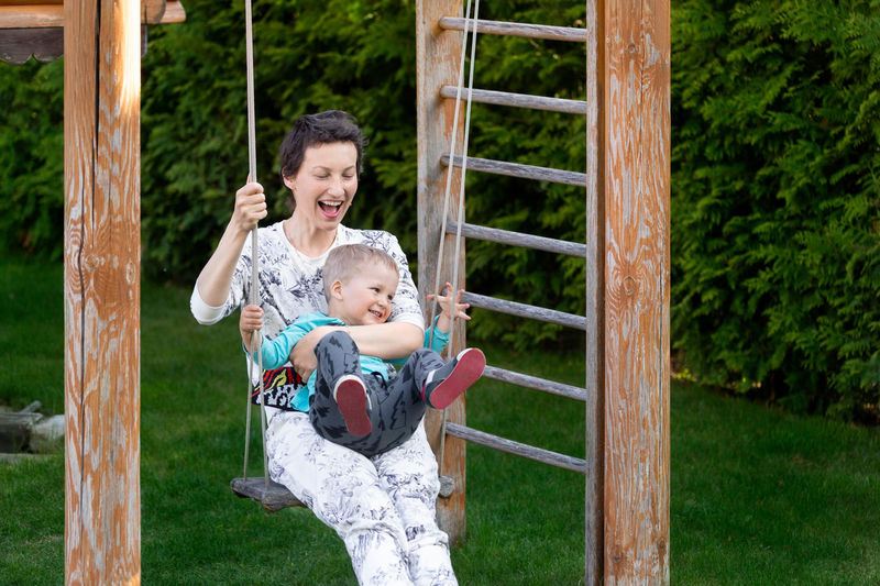 Cheerful woman with son swinging at park