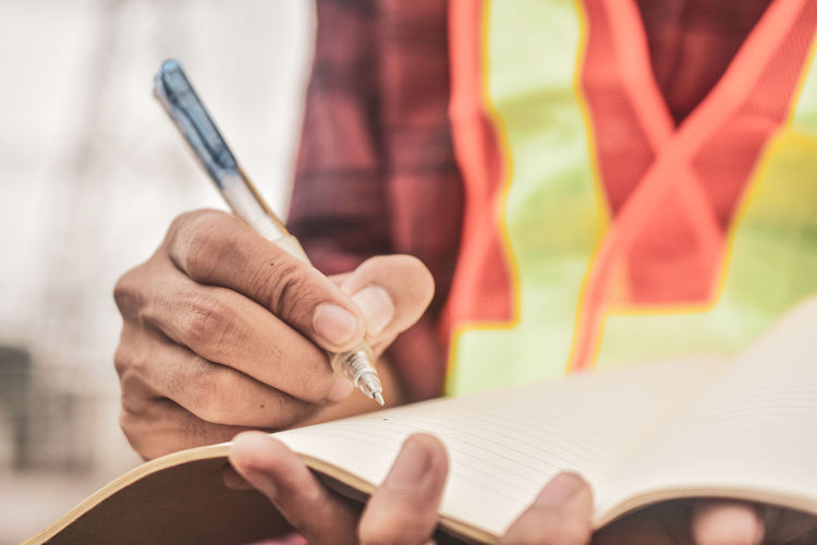 Midsection of worker writing on book