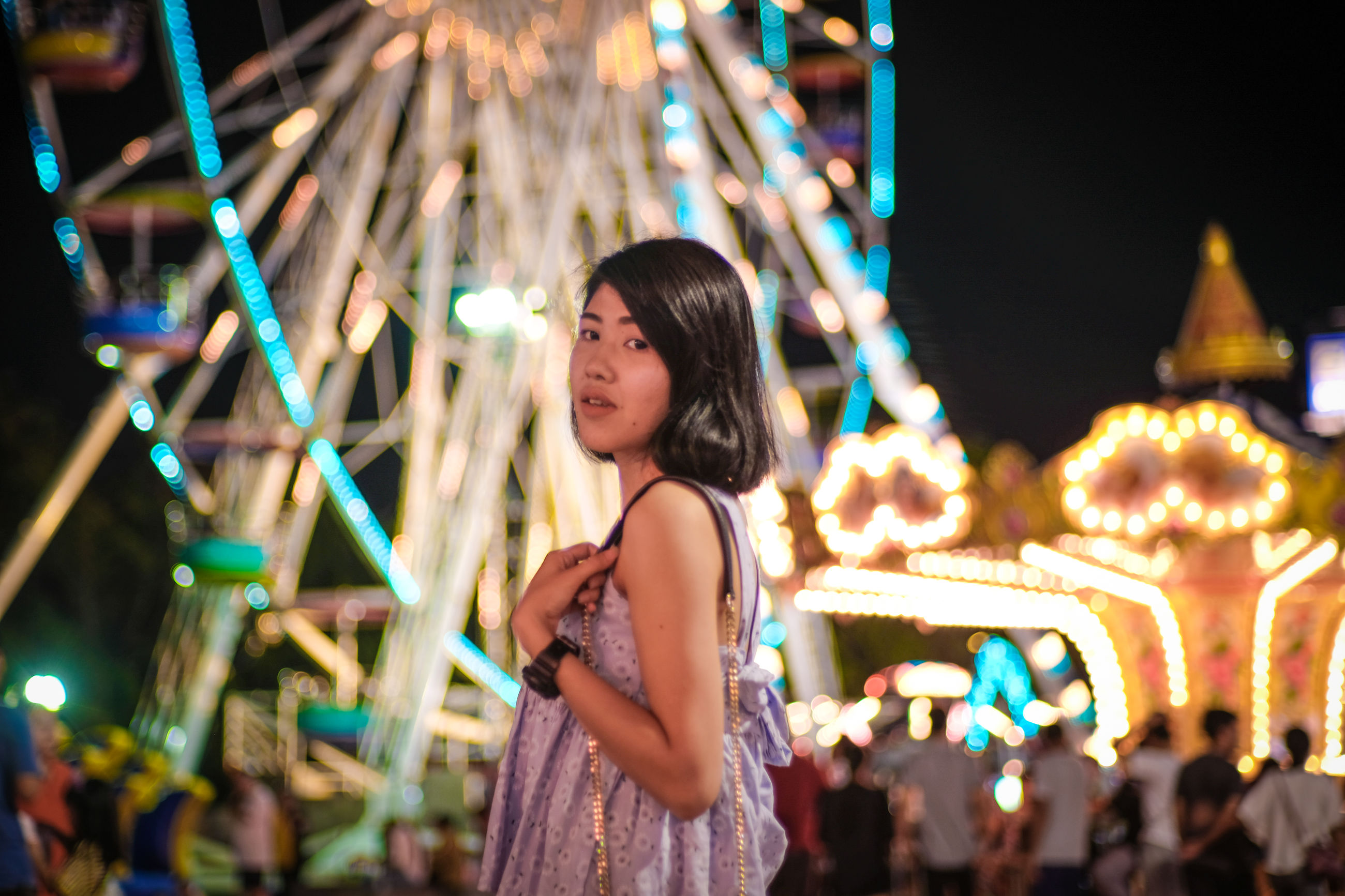 illuminated, night, real people, one person, women, leisure activity, lifestyles, focus on foreground, young women, incidental people, standing, young adult, adult, built structure, lighting equipment, architecture, casual clothing, amusement park ride, portrait, hairstyle, beautiful woman, light