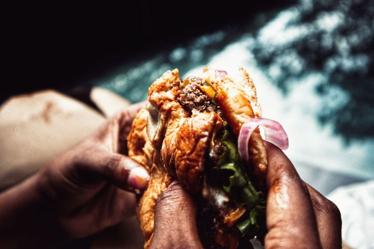 Someone's hands holding a burger that was bit into