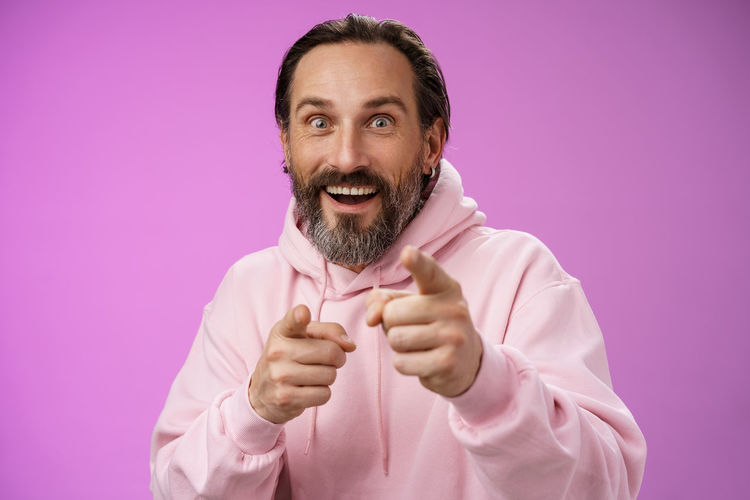 Portrait of smiling man wearing mask against pink background