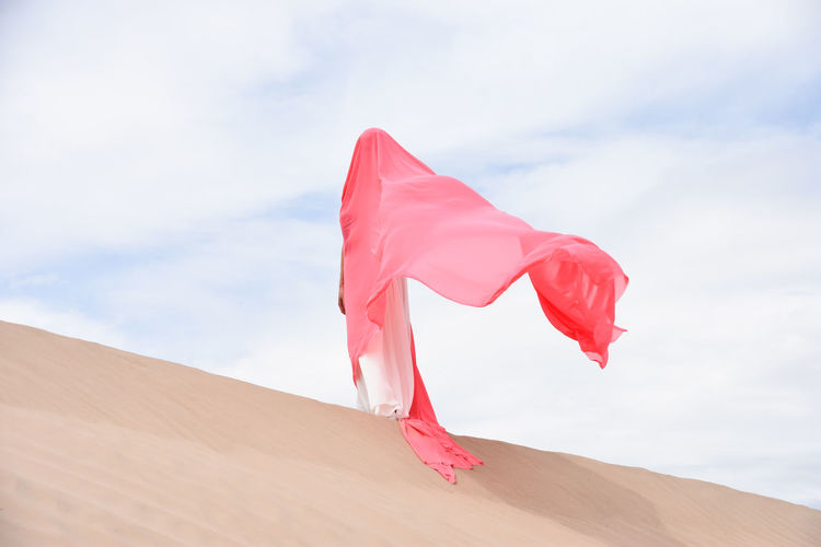 Caucasian woman standing in desert against blue sky, covered with pink fabric. face not visible.