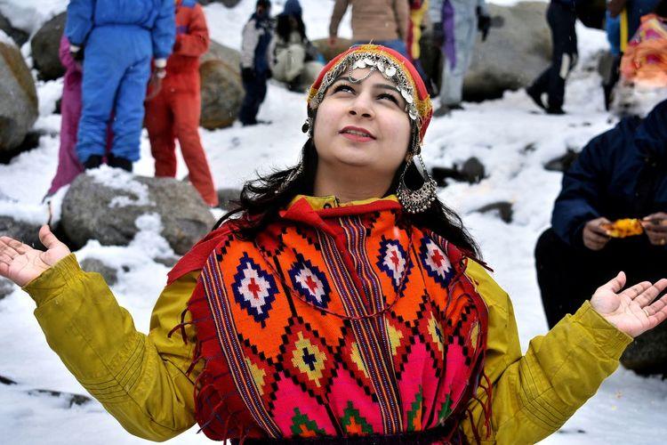 Beautiful girl posing, playing and enjoying snow in snow fall in manali india