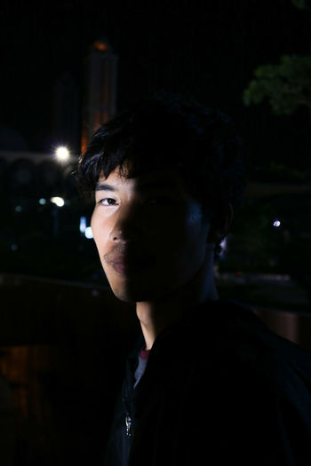 Portrait of man standing outdoors at night